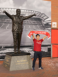 LIVERPOOL, ENGLAND - Tuesday, March 17, 2020: A supporter poses for a photograph in front of a statue of former Liverpool manager Bill Shankly at a near deserted Anfield, home of Champions-elect Liverpool Football Club, after the suspension of all football due to the Coronavirus (COVID-19) and Liverpool's decision to close it's Boot Room cafe and official stores. (Pic by David Rawcliffe/Propaganda)