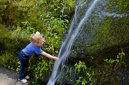 Young girl child next to stream water cascade over rock, Congress Trail, Giant Forest, Sequoia National Park, California