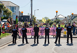 """© Licensed to London News Pictures; 13/06/2021; St Ives, Cornwall UK. G7 summit in Cornwall. Police hold a line as protesters hold a banner saying """"Tell the Truth"""" as Extinction Rebellion block the main road out of St Ives on the last day of the summit, protesting against climate change and what they say is not enough action by world leaders including those attending the G7. . Photo credit: Simon Chapman/LNP."""
