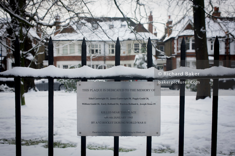 Local society plaque commemorating WW2 V2 victims on Court Lane Gardens in Dulwich Village during mid-winter snow.
