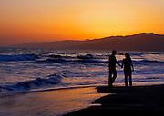 Couple In Love Walking Along Beach