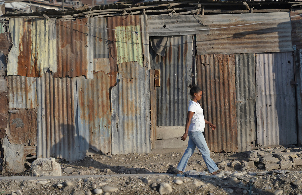 A woman walks past housing in Cite Soleil, a sprawling poor portion of Port-au-Prince, Haiti.