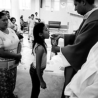 A young girl receive Holy Communion during mass at a church in Saravena, Aruaca, Colombia. Aruaca is a heavily disputed region being rich in oil and a main coca producing area. Control is fought for by two rebel groups; the ELN and the FARC as well as the rightwing AUC. There is a large presence of Government forces; some of whom have been trained by US Special Forces who are also based there.<br />