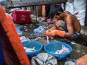 01 DECEMBER 2016 0 BANGKOK, THAILAND: A fish vendor cuts up fish in the traditional market on Lan Luang Road in Bangkok. The market is on the site of one of the first western style cinemas in Bangkok. The movie theatre closed years ago and is still empty but the market fills the streets around the theatre.     PHOTO BY JACK KURTZ