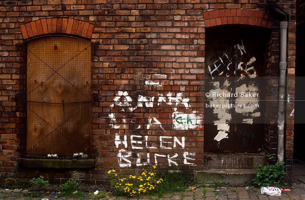 A filthy alleyway in Toxteth, Liverpool amid socially-deprived streets and terraced housing. Graffiti of girls' names has been painted on to the brick wall of a tenement building but is now peeling off. Weeds have grown around the cobbled pavement and the windows are boarded up in a landscape of urban dereliction and social depravity.