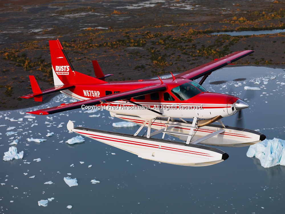 Rust's Flying Service Cessna 208 Caravan on floats flying above icebergs calved from Colony Glacier and floating in Lake George, Alaska.