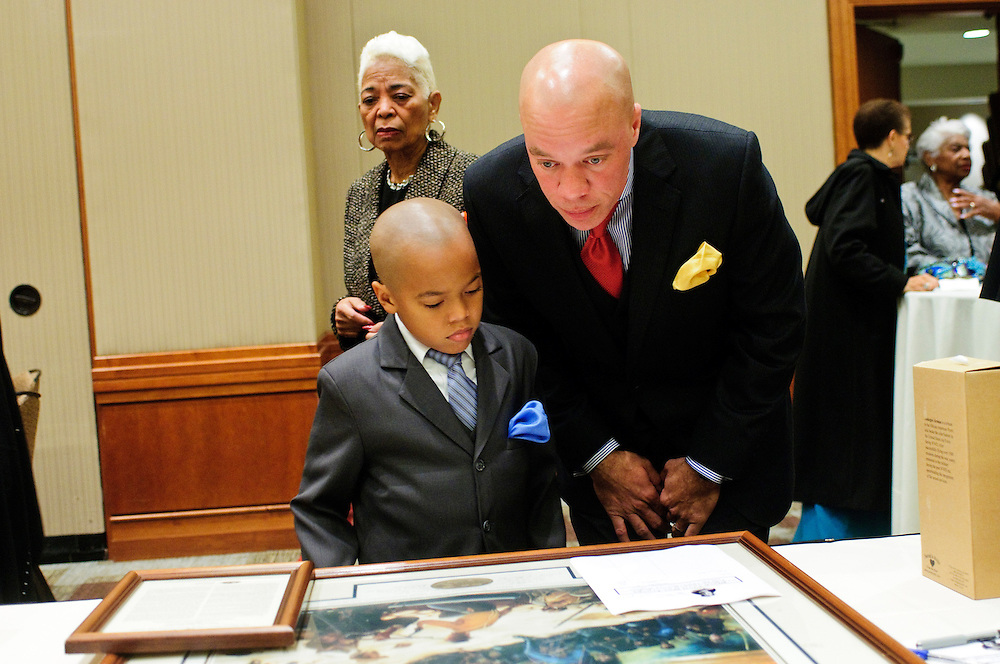Porter Jihaad, 8, shows his father Rakim a silent auction item that caught his eye during the second annual Gala for the Cause for Sainthood of Father Augustus Tolton at the Hyatt Regency McCormick Place on Friday, October 19th, 2012. The event is sponsored by The Archdiocese of Chicago's Office for Black Catholics, The Father Tolton Guild and the Office of Vicariate VI and Bishop Joseph Perry l Brian J. Morowczynski~ViaPhotos..For use in a single edition of Catholic New World Publications, Archdiocese of Chicago. Further use and/or distribution may be negotiated separately. ..Contact ViaPhotos at 708-602-0449 or email brian@viaphotos.com.   .The Archdiocese of Chicago's Office for Black Catholics hosts it's second annual Gala for the Cause for Sainthood of Father Augustus Tolton at the Hyatt Regency McCormick Place on Friday, October 19th, 2012. The event is co-sponsored by The Father Tolton Guild and the Office of Vicariate VI and Bishop Joseph Perry.