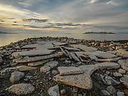 Concrete jetty at Saltaire near Salt Lake City on the Great Salt Lake is reduced to tatters from the freeze thaw of many winters with Antelope Island visible in distance.  Licensing and Limited Edition Prints.
