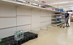 © Licensed to London News Pictures. 03/08/2021. London, UK. A shopper wearing a face covering looks at empty shelves of bottled drinking water in Sainsbury's, north London. It has been reported that Britain could face a shortage food and drink supplies and these are likely to continue for several months, due to a lack of lorry drivers. Photo credit: Dinendra Haria/LNP