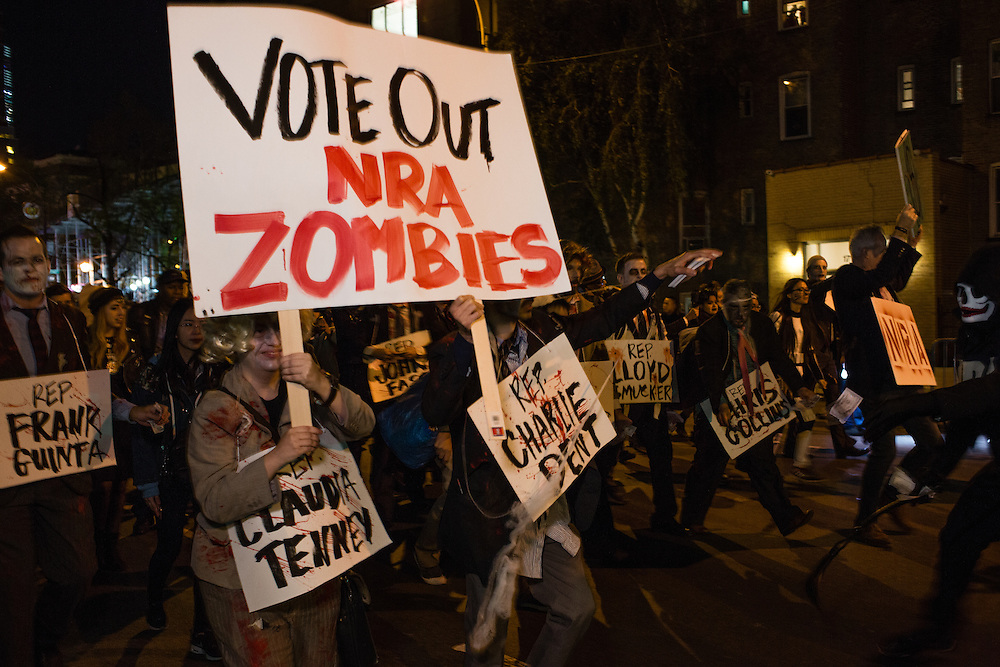 """New York, NY - 31 October 2016. Marchers with Gays Against Guns in the annual Greenwich Village Halloween Parade carried signs such as this one, which reads """"Vote Out NRA Zombies,"""" and which often mentioned particular members of congress."""
