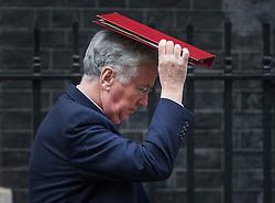 © Licensed to London News Pictures. 01/03/2016. London, UK.  Michael Fallon , Defence Secretary, protects his head from the rain as he leaves Downing Street after attending a cabinet meeting. Photo credit: Peter Macdiarmid/LNP