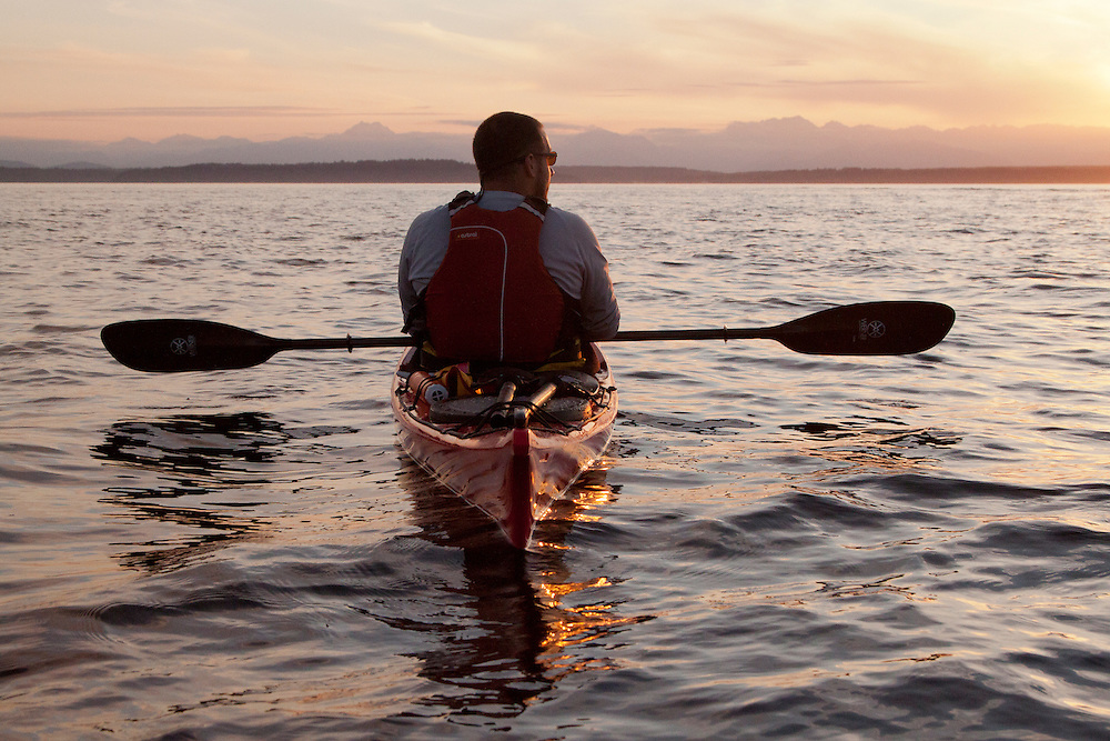 North America, United States, Washington, man at rest in kayak at sunset.  MR