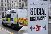 Police van passes a social distancing sign along Regent Street as the national coronavirus lockdown three continues and all non-essential shops have to remain closed on 3rd March 2021 in London, United Kingdom. With the roadmap for coming out of the lockdown has been laid out, this nationwide lockdown continues to advise all citizens to follow the message to stay at home, protect the NHS and save lives, and the streets of the capital are quiet and empty of normal numbers of people.