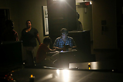 October 7, 2016 - Titusville, Florida, U.S. - WILL VRAGOVIC   |   Times.Under the glow of emergency lights, Adam Lowenstein, 45, and his son Joshua, 8, check text messages and wait out Hurricane Matthew in the lobby of the Hampton Inn in Titusville, Fla. on Friday, Oct. 7, 2016. The Lowenstein's evacuated their Merritt Island home on Thursday. ''We're really worried about our house,'' Adam said, ''We had to leave our cats, so obviously we're also worried about them. (Credit Image: © Will Vragovic/Tampa Bay Times via ZUMA Wire)