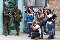 Fotojornalistas e cinegrafistas acompanhados dos soldados do Exército Brasileiro na entrada da favela Morro do Alemão, em 27 de novembro de 2010 no Rio de Janeiro, Brasil.. Centenas de soldados e policiais se juntaram para uma repressão sobre as gangues de drogas. No início desta semana, a polícia forçou os membros das gangues saírem da favela Vila Cruzeiro, com o auxílio de tanques M113 transportadores blindados de pessoal. FOTO: Jefferson Bernardes/Preview.com