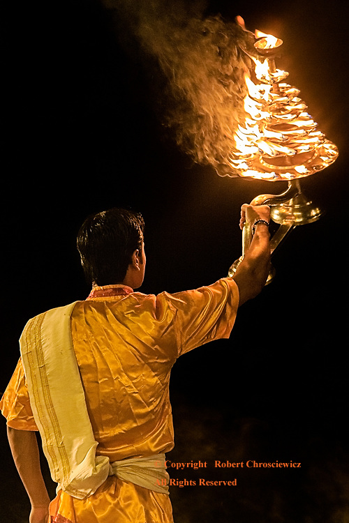 """Worship to Fire: A Hindu priest perform the Aarti Ceremony -the """"Agni Pooja"""" (Worship to Fire), using an elaborate fire bearing vessel, at Assi Ghat, Varanasi India."""