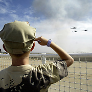 A child salutes as military helicopters fly by at the Miramar Air Show in San Diego, CA. Model released.