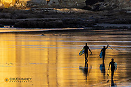 Surfers and standup paddleboarders head out for action at sunrise at Cape Kiwnada in Pacific City, Oregon, USA