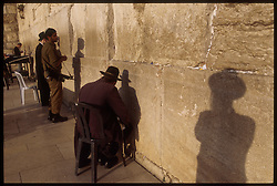 EAST JERUSALEM - NOVEMBER 15, 2000 - Orthodox Jews pray at the Western Wall, despite the ongoing violence, which has kept many of the faithful away. Control over East Jerusalem, where many of the holiest sites of the Jewish, Muslim and Christian faiths are located, continues to be a major point of contention in the ongoing peace negotiations.  (PHOTO © JOCK FISTICK)