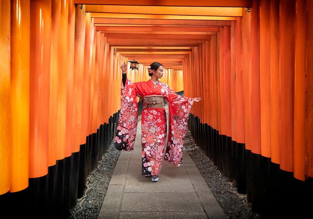 Tourist wearing traditional kimono dress poses for a portrait in a tunnel of Tori Gates at Fushimi Inari Taisha in Kyoto, Japan.