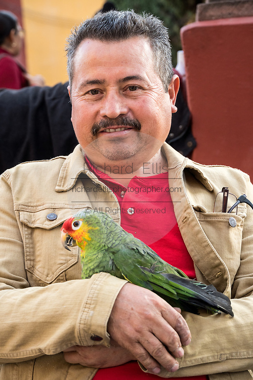 A man carries his pet parrot as he waits for the start of the annual blessing of the animals on the feast day of San Antonio Abad at Oratorio de San Felipe Neri church January 17, 2020 in the historic center of San Miguel de Allende, Guanajuato, Mexico.