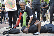 "6/6/2020 Jackson MS. <br /> Pictured is Barbara Walker with her knee on the neck of National Black Panther Party Kelvin Bradfield out side the Governor Mansion after a peaceful protest by Black Lives Matter, organized by 18yr old student Maisie Brown. Bradfield chanted ""I can't breathe "" as the crown chanted _check his pulse.""as Walker held her knee on his neck in the 90 degree heat. Photo© Suzi Altman<br /> <br /> Student Maisie Brown 18yrs old from Jackson organized a peaceful protest outside the Governors Mansion. She said there voices would be heard and her face would be seen- change is coming. The protest was in honor of George Floyd and in support of ending systematic racism and to end police brutality in Mississippi and America. The National Black Panthers Party from Tupelo Mississippi showed up outside the Governors mansion in the shadow of the State Capitol to protest police brutality. The National Black Panthers Party was their to show their support for change in Mississippi, to end systemic racism and police brutality. Protests have broken out around the world in solidarity to end white supremacy and police brutality. The Panthers showed up at the end of a peaceful protest organized by 18yr old student Maisie Brown. The brutal murder of African American George Floyd by the knee and hands of 4 former Minneapolis Minnesota police officers has sparked a cry for justice and reform around the world. Photo copyright © Suzi Altman @suzialtman #mississippi #blm #blacklivesmatter #protest #icantbreathe #georgefloyd #endracism #policebrutality #documentary #history #suzialtman #iphonography #shotoniphone #zumapress #NBPP #panthers #blackpanthers #nationalblackpantherparty"