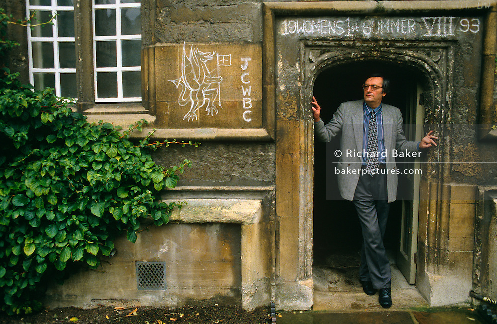 With student graffiti on the classical architecture,  John Gray the political scientist, stands in a doorway wearing a grey jacket and his round-frame glasses in the Quadrangle of Jesus College, Oxford. He is a prominent British political philosopher, author and currently School Professor of European Thought at the London School of Economics. Prior to this he was Professor of Politics at Oxford University. He is a former supporter of the New Right and a regular contributor to the Guardian and the Times Literary Supplement. Also author of many books on political theory. He has written several influential books on political theory, including Straw Dogs: Thoughts on Humans and Other Animals (2003), an attack on humanism, a worldview which he sees as originating in religious ideologies. .....