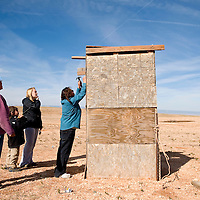 032713     Brian Leddy<br /> Marsha Monestersky install a small solar light on the outhouse of the Wilson residence Wednesday, March 27.