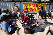 Spring community activities on The Southbank, London. Family relaxes in the sunshine by a sign that says Fish and Chips. British seaside in central London, on a 70-metre urban beach that appears on Queen's Walk for the duration of the Festival of Britain celebrations.