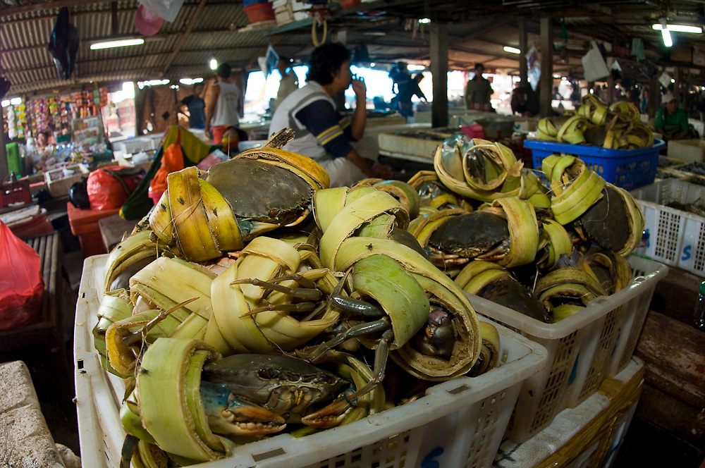Cratefuls of crabs, wrapped in leaves, await buyers in one of Bali's fish markets.