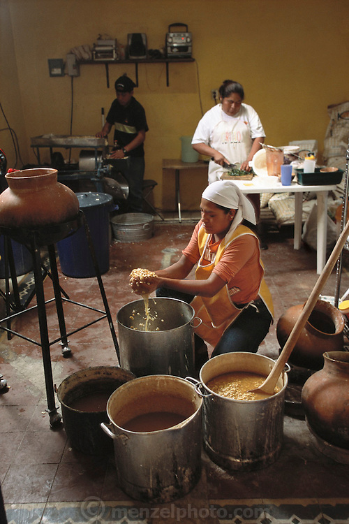 """The Itanoni Tortilleria (""""Gourmet Tortillas"""") in Oaxaca, Mexico sells handmade tortillas from native corn that it contracts local growers to produce. In the back room, workers wash dried corn after cooking it. It is then ground into a moist flour that is pressed into tortillas and cooked on clay oven tops, called """"comals""""."""