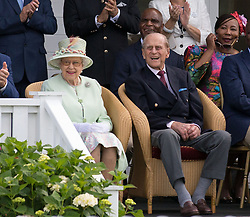 Queen Elizabeth II and the Duke of Edinburgh watch a British Driving Society parade during the Bentley Motors Royal Windsor Cup Final at Guards Polo Club, Windsor Great Park, Egham, Berkshire.