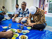 13 JULY 2013 - BANGKOK, THAILAND:  A man prays while others socialize before Iftar (the Muslim meal that breaks the day long fast) during Ramadan. Ramadan is the ninth month of the Islamic calendar, and the month in which Muslims believe the Quran was revealed. The month is spent by Muslims fasting during the daylight hours from dawn to sunset. Fasting during the month of Ramadan is one of the Five Pillars of Islam. Muslims believe that the Quran was sent down during this month, thus being prepared for gradual revelation by Jibraeel (Gabriel) to the prophet Muhammad.        PHOTO BY JACK KURTZ