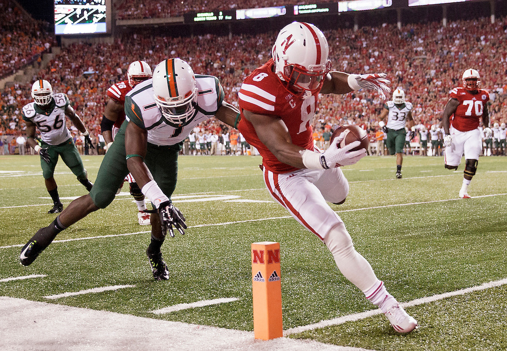 Nebraska I-back Ameer Abdullah (8) rushes into the end zone past Miami defender Artie Burns (1) for a touchdown with 7:10 left in the second quarter of Saturday's game at Memorial Stadium in Lincoln. (Independent/Matt Dixon)