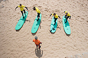 A male surf instructor teaches four learner surfers to stand on a surfboard at Matadouro beach on 26th May 2018 in Ericeira in Portugal. Ericeira is a civil parish and seaside resort/fishing community on the western coast of Portugal.