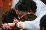 Twee bezoekers ondergaan de darshan, oftewel de omhelzing, door Amma. In de Expo in Houten is Mata Amritanandamayi, beter bekend als Amma of 'hugging mother', aanwezig om mensen te omhelzen en te inspireren. Het driedaags benefiet in Houten is het grootste spirituele festival in Nederland en zal naar verwachting 15.000 bezoekers trekken.<br /> <br /> Two visitors are receiving the darshan from Amma. In the Expo in Houten people are gathering to get a darshan, or hug, by  Mata Amritanandamayi, also known as Amma or 'hugging mother'. Amma is travelling through the world to hug people for inspiring them to make a better world. Amma is one of the twelve most influence spiritual leaders of the world. The event in Houten lasts for three days and is the biggest spiritual event of The Netherlands.