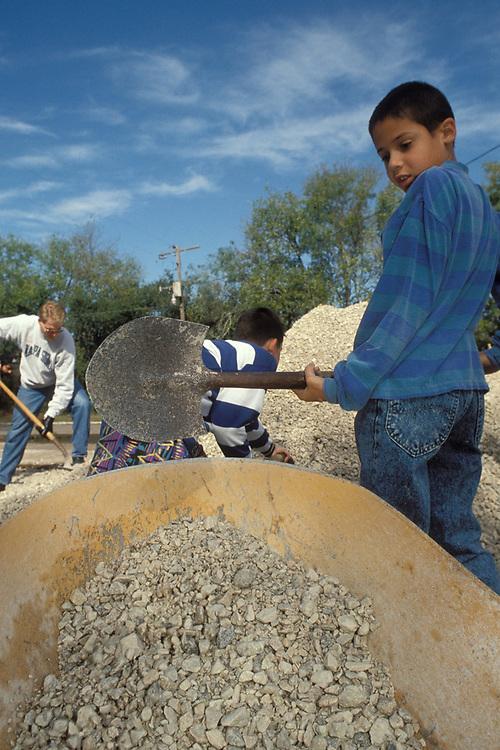 Hispanic young boy shoveling rocks to help build neighborhood playscape.<br /> ©Bob Daemmrich/