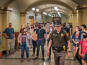 15 JUNE 2020 - DES MOINES, IOWA: An Iowa State Trooper walks through a crowd of Black Lives Matter protesters in the Iowa capitol in Des Moines. About 75 supporters of Black Lives Matter marched through the Iowa capitol Monday to demand the restoration of voting rights for felons who have completed their sentences. Iowa is one of only two states in the US that permanently strip felons of voting rights. The issue is a  racial one in Iowa. Blacks make up only 4 percent of the population but 25 percent of the prison population. The Governor agreed to meet with a delegation of the protesters but she would not commit to immediately restoring voting rights. She said would draft an executive order to restore voting rights later in the summer.     PHOTO BY JACK KURTZ