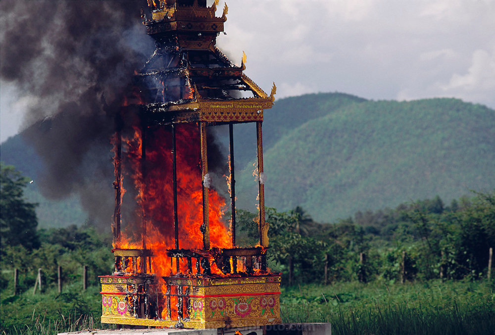 After the death of a 72-year old man who lived across the road from the Khuenkaew family of the Material World Project, his family followed Thai tradition and bought a castle-like, wood-and-crepe paper funeral bier and placed the body on top. Then the village held a two-day wake, complete with tents, music, gambling, and outdoor barbecues. Gifts were piled atop the casket. Afterward, the men carried the bier on long bamboo poles to the cemetery. The family posed for photographs in front of the bier, said good-bye to the dead man, and left the cemetary-keeper to burn the remains. Published in Material World: A Global Family Portrait. pages 86 & 87. Thailand.