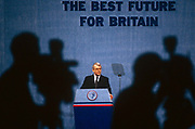 Prime Minister of the day,  John Major is under the scrutiny of media TV cameras during the 1991 Tory party conference. The silhouettes of two TV cameramen both peering through the viewfinders of their video equipment are seen out of focus in the foreground while Major pauses momentarily during his important speech of that year's conference (convention). Major (born 29 March 1943) is a British Conservative politician who served as Prime Minister of the United Kingdom and Leader of the Conservative Party from 1990–1997. He held the posts of Foreign Secretary and Chancellor of the Exchequer in the cabinet of Margaret Thatcher and was MP for Huntingdon 1979–2001.