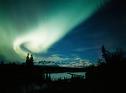 Beautiful display of northern lights arcing over the Alaska Range including Mouont McKinley or Denali with the Chulitna River in the foreground, Denali State Park, Alaska.
