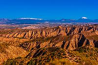 Badlands, seen from the Mirador Cueva los Amos viewpoint with snowcapped La Sagra peak in background, near Castillejar, Granada Province, Andalusia, Spain.