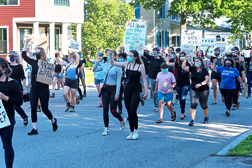 Bar Harbor, Maine, USA. 06 July, 2020. Marchers in a protest led by the Mount Desert Island Racial Justice Collective walk silently down Ledgelawn Avenue with a fist raised in support of Black Lives Matter.
