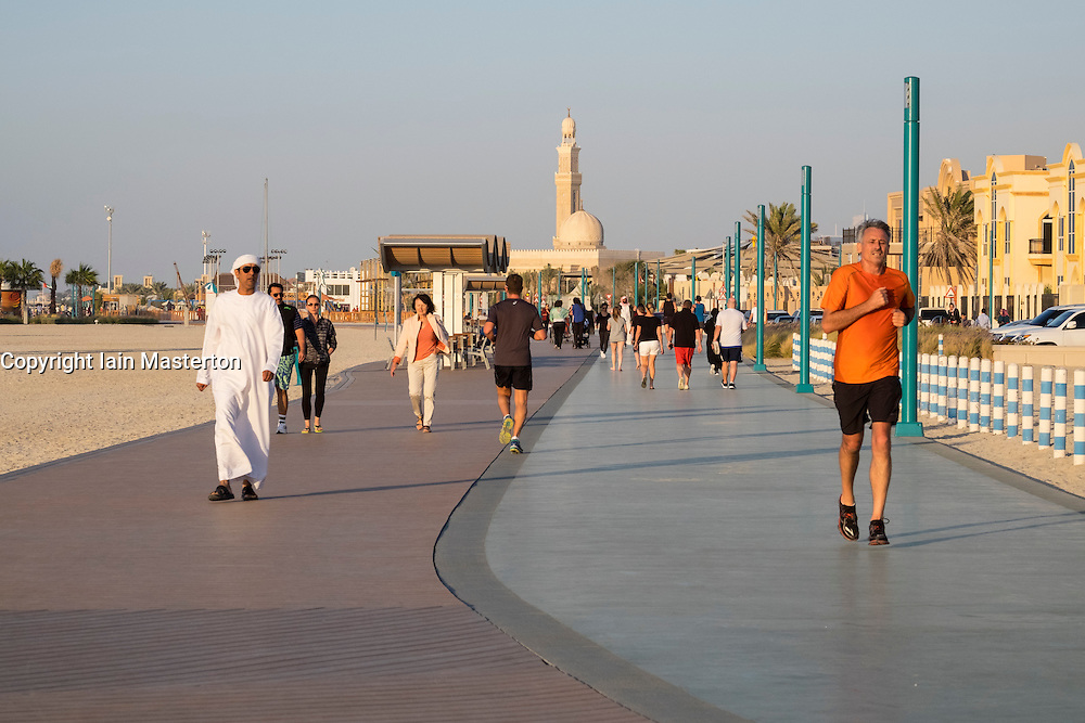 Many people using new public boardwalk and jogging track beside beach   in Dubai United Arab Emirates