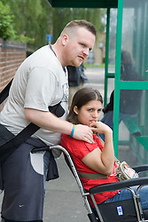 Young woman with Cerebral Palsy in a wheelchair with her boyfriend waiting for a bus,