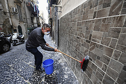 Man wearing a protective mask, washing a wall in the Spanish quarter, in Naples city, Italy on March 14, 2020, after a government decree declaring all of Italy a protected area to combat covid-19 coronavirus infection. Photo by Salvatore Laporta/IPA/ABACAPRESS.COM