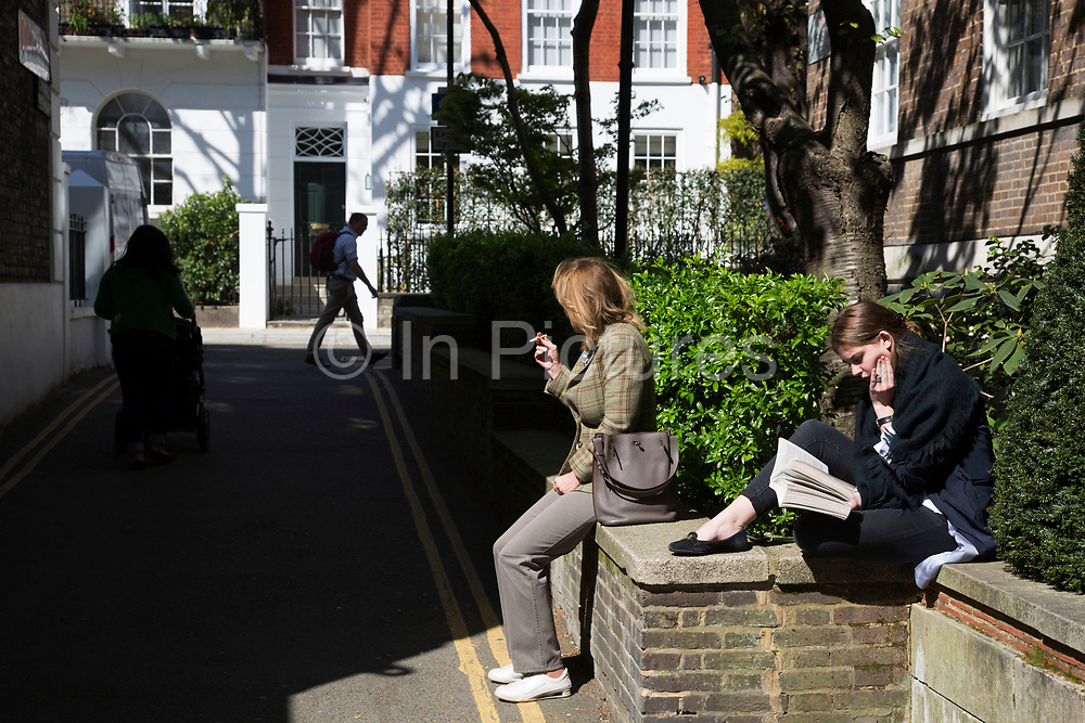 Woman reading on Kensington Church Walk. In a selected few boroughs of West London, wealth has changed over the last couple of decades. Traditionally wealthy parts of town, have developed into new affluent playgrounds of the super rich. With influxes of foreign money in particular from the Middle-East. The UK capital is home to more multimillionaires than any other city in the world according to recent figures. Boasting a staggering 4,224 'ultra-high net worth' residents - people with a net worth of more than $30million, or £19.2million.. London, England, UK.