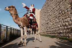 December 21, 2017 - Jerusalem, Israel - Santa Claus, or 'Baba Noel' as he is called in Arabic, rides a camel substitute for rain deer near Jerusalem's Old City Jaffa Gate. The Jerusalem Municipality and the Jewish National Fund distributed specially grown Arizona Cypress Christmas trees to the Christian population at the Jaffa Gate. (Credit Image: © Nir Alon via ZUMA Wire)