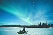 Alaska. Petersville. Snowmachiner and Northern lights (aurora borealis). MR.