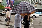 Passanten mit Regenschirmen in einem Viertel mit Bank Hochhaeusern im Zentrum der koreanischen Metropole Seoul. <br /> <br /> Passersby with umnrellas in a quater with bank towers in the center of the Korean metropolis Seoul.
